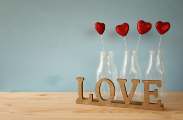 Glitter hearts in the glass vases on wooden table