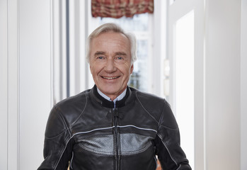 Portrait of smiling senior man in motorcycle suit