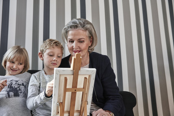 Grandmother and grandson with Dali moustache at easel with girl watching