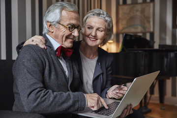 Happy senior couple shopping online at home