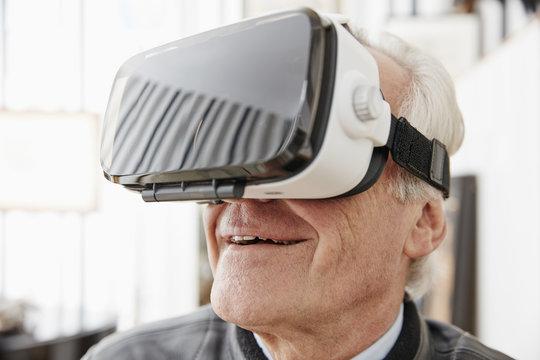 Senior man wearing VR glasses