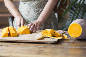Woman chopping pumpkin for preparation of raw pumpkin noodles