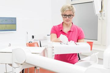 Junge blonde Zahnarzthelferin bereitet Instrumente für Behandlu