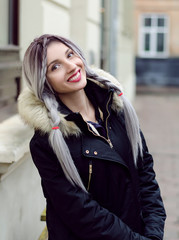 Beautiful young girl with silver gray braid hair, red lips wearing black down jacket walking on the street in warm winter. Close up lifestyle portrait