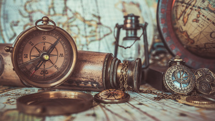Old vintage retro compass, magnifying glass and glass oil lamp on ancient world map. (vintage style)