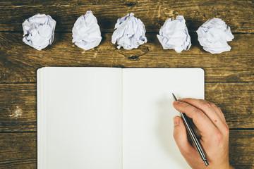 Ein leeres Buch, ein rustikaler Tisch und eine Hand zum Schreiben