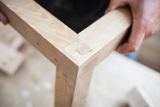 Detail of a furniture maker holding an example of his intricate