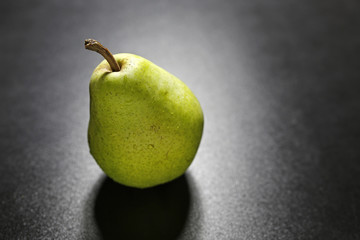 pear with water drops on black background