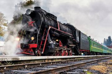 Rare steam train locomotive preparing for departure from railway station