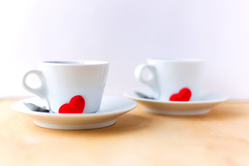 Couple cups decorated by red hearts on wooden table.