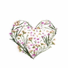 Heart symbol made of pink wildflowers. Flat lay, top view. Valentine's background.