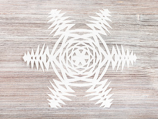 snowflake cut out of paper on light brown plank