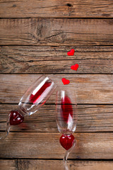 Two glasses in Heart shape with Red Wine on Old Wooden Background. Holiday Valentine's Day.Still Life.Toned image.Vintage style.selective focus.