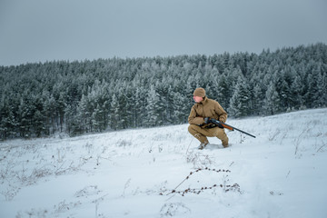 Hunter man dressed in camouflage clothing standing in the winter