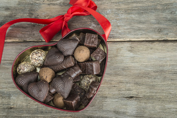 valentine day concept/box shaped heart with chocolats on old wooden background top view with space for text