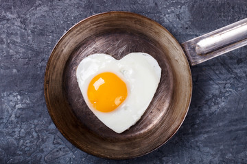 Fried egg in heart shape on the pan.Holiday Valentine's Day.Breakfast. Healthy Food.selective focus.