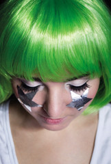 portrait of a girl with green hair and stars on her cheeks eyes closed