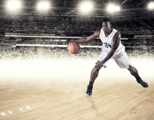 A strong athletic professional basketball player skillfully dribbling up the court. Clean white background. Lots of copy space