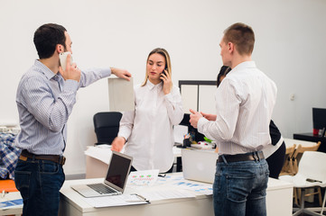 Group of four diverse cheerful co-workers taking self portrait and making funny gestures with hands at small office