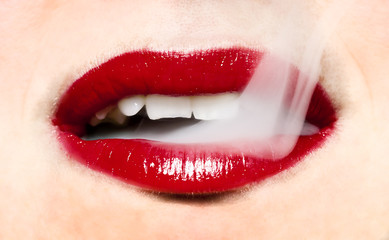 Smoke coming from mouth. Woman with bright red lips.