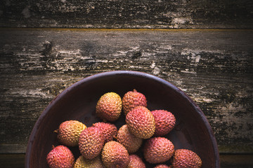 Sweet lychee fruit in a bowl on a background of old wood