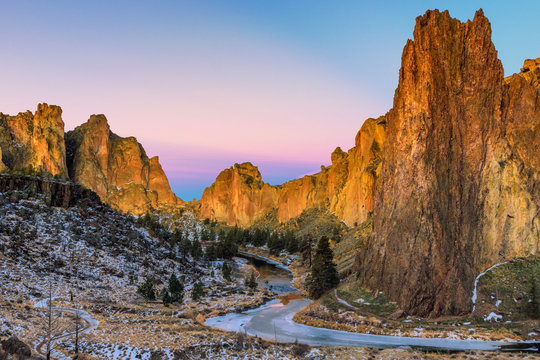 Winter sunrise at Smith Rock State Park with a dusting of snow and a frozen Crooked River.