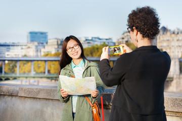 Woman taking photo of her friend near Seine