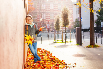 Boy standing in leaf pile, holding autumnal bunch