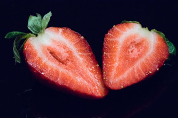 Single sliced strawberry isolated on black