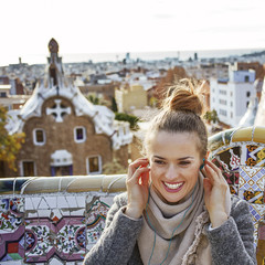 woman in Barcelona listening audioguide while sitting on bench