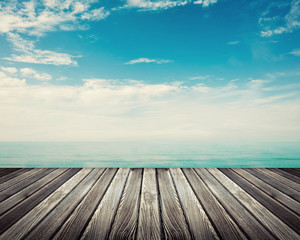 Wooden deck floor against ocean with cloudy sky in background