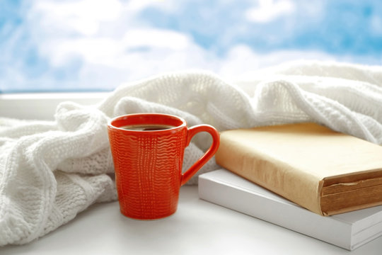 Cup of fresh coffee with books and knitted plaid on windowsill