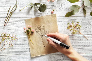 Female hand drawing flower on paper on white wooden background