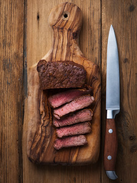 Single roasted medium rare sliced flank beef piece with herbs over wooden bord