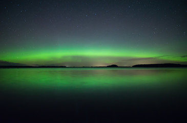 Northern lights dancing over calm lake
