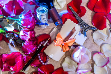 holiday concept - roses petals, money, bottles of wine, a box of jewels and Eiffel Tower.