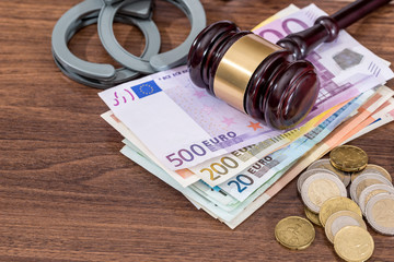 handcuffs with law hammer and euro bills, coin on desk. business concept.