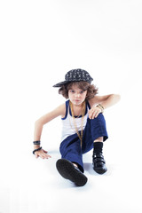 Little curly boy in fashionable clothes sitting on the floor and looking into the camera. White background.