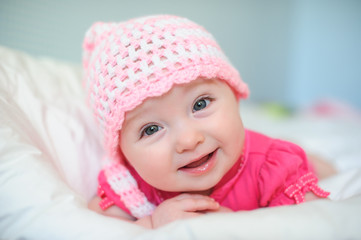 little girl in a knitted hat lying on the bed