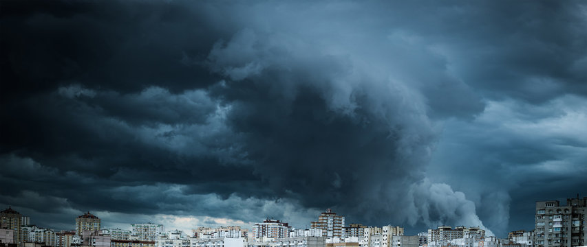 Dramatic stormy clouds over residential buildings. Panorama of the city with dark and powerful clouds.