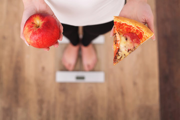 Diet. Woman Measuring Body Weight On Weighing Scale Holding Pizza. Sweets Are Unhealthy Junk Food. Dieting, Healthy Eating, Lifestyle. Weight Loss. Obesity. Top View