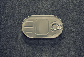 canned closed in an oval box on a gray background, view from above