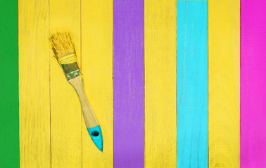 Brush in yellow paint on wooden background with green, yellow, blue, purple and rose planks