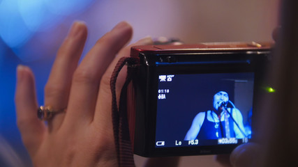 Photographer woman's hand holding gadget during a rock-concert