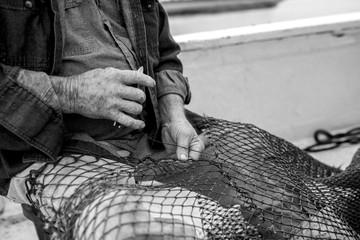 Hands of weathered fisherman mending net