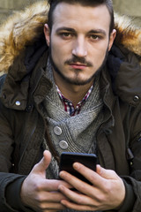 young man sitting with mobile phone