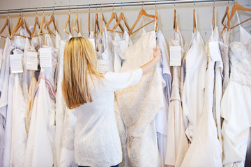 Bride: Woman Browsing Through Rack Of Wedding Gowns