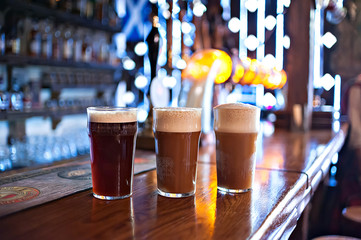 three varieties of freshly brewed natural beer on a dark pub