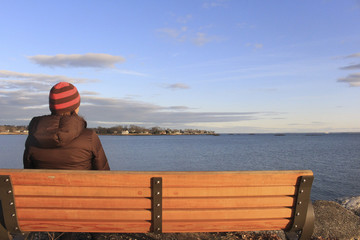 woman on bench at sunset looking at ocean