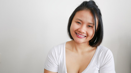 Asian woman wearing white t-shirt smiling on white background